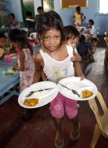 A girl carrying her younger sister on her back collects their free meals during a feeding program at a slum area in Baseco, Tondo city, metro Manila May 22, 2013. (MNS photo)