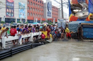Residents catch tilapia at Panapaan Bridge, Barangay Habay I in Bacoor, Cavite on Thursday (August 22, 2013) as heavy flooding persists in Metro Manila and nearby provinces due to the enhanced southwest monsoon. (MNS photo)