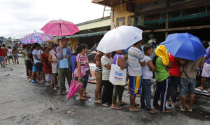 Survivors of Typhoon Haiyan line up to buy food in front of a grocery store which has not been looted, along a street in the typhoon devastated town of Palo, near Tacloban November 16, 2013.  (MNS photo)