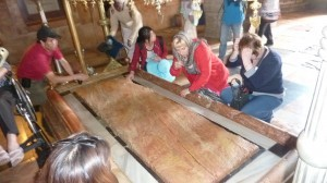 """GOLGOTHA, JERUSALEM: Pilgrims from the U.S. to the """"place of skull in Golgotha, Jerusalem where Jesus' body was given the rightful pre-burial customary treatment marvel at the slab where the ceremony took place. Christians worldwide will celebrate His birth on December 25 amid the tumultuous state of the world that He offered Himself to save."""