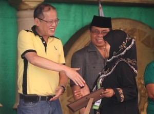 """President Benigno S. Aquino III distributes vouchers for Scholarship Grants to beneficiaries during the Ceremonial Launch of Sajahatra Bangsamoro Program: Peace Dividends of the Framework Agreement on the Bangsamoro (FAB) at the Bangsamoro Leadership and Management Institute (BLMI) in Barangay Salimbao, Sultan Kudarat, Maguindanao on Monday (February 11, 2013). The strong partnership between the government (GPH) and the Moro Islamic Liberation Front (MILF) has become more evident as both sides work together in the process of identifying beneficiaries and their immediate needs that will be addressed by the Sajahatra Bangsamoro program. The FAB indicated that """"the Parties agree to intensify development efforts for rehabilitation, reconstruction, and development of the Bangsamoro, and institute programs to address the needs of MILF combatants, internally displaced persons, and poverty-stricken communities."""" In photo is MILF chairman Al Haj Murad Ebrahim. (Photo by: Ryan Lim / Malacañang Photo Bureau)."""