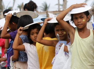 Children hold plates on top of their heads against rainfall as they queue for free meals during Christmas celebrations at the town of Bislig, Tanauan in Leyte province, central Philippines December 24, 2013, a month after Typhoon Haiyan battered central Philippines. Super typhoon Haiyan reduced almost everything in its path to rubble when it swept ashore in the central Philippines on November 8, killing at least 6,069 people, leaving 1,779 missing and 4 million either homeless or with damaged homes. (MNS photo)