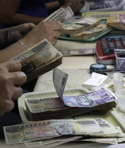An employee counts Philippine pesos inside a money changer in Manila September 19, 2013. A Philippine official said a weaker peso will benefit Philippine exporters by making their products less expensive and thus more competitive in the global market.