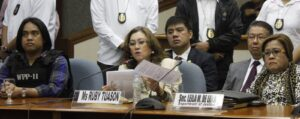State witness Ruby Tuason reads her opening statement during the Feb. 13, 2014 Senate Blue Ribbon Committee hearing on the alleged pork barrel scam as Justice Secretary Leila del Lima (right) and whistle-blower Benhur Luy (left) listen. (MNS photo)