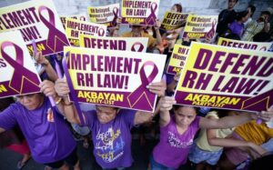 Protesters display placards during a rally March 19 at the Philippine Supreme Court in Manila to protest the court's issuance of a 120-day status quo ante order, or a four-month delay, of the implementation of the Reproductive Health Law. (AP photo/Bullit Marquez)