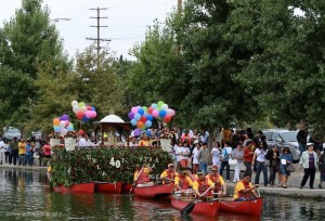 """The Virgin's statuette on a """"pagoda"""" barge decorated with flowers and balloons and rowed around the park lake, followed by a foot procession on the lake's perimeter amid rosary prayers, Marian hymns and shouts of """"Viva la Virgen!""""."""