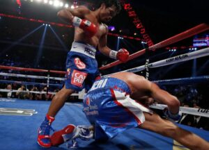 Chris Algieri of the U.S. falls as he takes a punch from Manny Pacquiao (left) of the Philippines during their World Boxing Organization (WBO) 12-round welterweight title fight at the Venetian Macao hotel in Macau November 23, 2014.(MNS photo)
