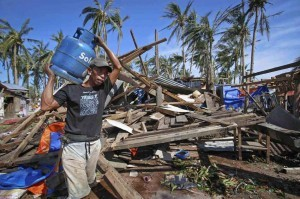 A typhoon victim carries a cooking gas tank past a house destroyed by typhoon Ruby in Borongan, Samar on Monday. More than a million people were evacuated as the powerful typhoon approached the country, fearing a repeat of last year's typhoon that left 7,000 dead or missing.  (MNS photo)