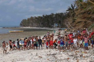 Typhoon victims wait for relief supplies on a beach in a remote village in Dolores, Eastern Samar on Tuesday. Typhoon Ruby barreled across central Philippines and devastated remote villages making it hard for government response teams to reach the areas.(MNS photo)