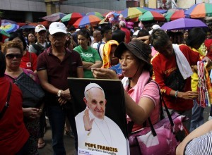 A vendor joins a crowd of churchgoers outside the Quiapo Church in Manila to sell calendars bearing the photo of Pope Francis on Friday (Jan. 2, 2015). The Pontiff is arriving in Manila on Jan. 15, 2015 for a four-day Apostolic and State Visit to the Philippines. (MNS photo)