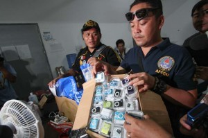 An operative of a joint inter-agency government task force holds counterfeit music players raided from a warehouse in Binondo, Manila on Wednesday. The raid netted fake cellphones, electronic gadgets, and accessories worth an estimated P70 Million.  (MNS photo)