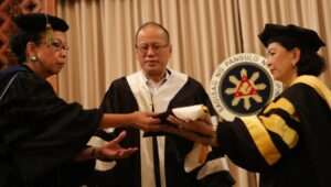 President Benigno S. Aquino III, assisted by Tarlac State University (TSU) president Dr. Myrna Mallari and Commission on Higher Education (CHED) chairperson Patricia Licuanan, dons an academic gown, hood, cap and medal during the Conferment of the Degree of Doctor of Humanities (Honoris Causa) at the Reception Hall of the Malacañan Palace on Thursday (May 14, 2015). (MNS photo)