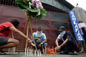 Members of labor groups light candles on Friday as they hold a sympathy protest in Valenzuela City, in front of the gates of Kentex footwear factory. They urged the government to take legal action against the company's owners and local officials for the death of 72 workers in the fire that razed the factory. (MNS photo)