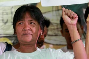 Celia Veloso, mother of Mary Jane Veloso, raises her fist before answering questions at a briefing at the Migrante headquarters on Friday. She blames the Philippine government for her daughter's conviction and death sentence for trafficking illegal drugs in Indonesia.  (MNS photo)