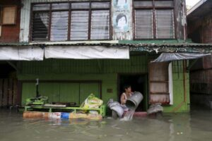 A woman clears flood water that entered her home, caused by tropical storm Egay at Longos town in Malabon City on Monday. Classes were suspended in Metro Manila and 14 areas in Luzon due to flooding and landslides while all shipping and flights were canceled as Egay moved slowly accross the country.(MNS photo)