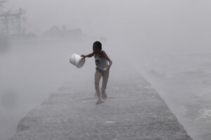 A boy runs as heavy rains and high waves brought by tropical storm Egay crash along a breakwater in Baseco, Tondo in Manila on Monday.  Storm warnings were issued in at least 14 areas as Egay, carrying maximum wind gusts of 100 km per hour, moved slowly across the Luzon island. (MNS photo)