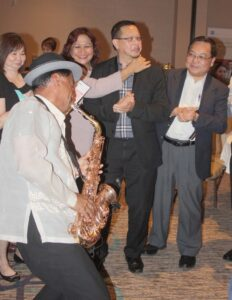 Jazzing Up for 117th  Philippine Independence: A Fil-Am sax virtuoso whips it up entertaining  guests (Romy and Gloria Rull and Dr. Tony Reyes, at right, ) at the Filipino American Chamber of Commerce in Orange County event to celebrate the Phillippines' Independence Day.