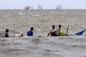 Fishermen on a small boat sail through rough waves caused by Typhoon Ineng, at Manila Bay, Thursday. Typhoon Ineng on Thursday packed maximum sustained winds of 180kph near the center with gusts of up to 215kph as it moves closer to extreme northern Luzon, PAGASA said. (MNS photo)