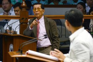 -- Senate Minority Leader Juan Ponce Enrile questions Sen. Sonny Angara during a session on tax issues at the Senate on Tuesday. Enrile returned to work Monday, after posting P1.45-million bail for plunder and graft charges filed against him. (MNS photo)