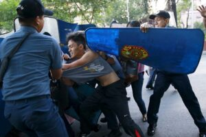A riot police officer uses his shield to stop a protester during a rally against the Enhanced Defense Cooperation Agreement (EDCA) in front of the U.S. embassy in Manila on Wednesday. The deal between the U.S. and Philippine governments would allow U.S. forces access to Philippine bases. (MNS photo)